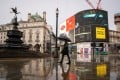 A man with an umbrella walks through Piccadilly Circus in London. Photo: DPA