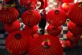 A vendor of Lunar New Year decorations looks up near giant lanterns hung outside a store ahead of the Year of the Ox Chinese Lunar New Year celebrations in Wuhan in central China's Hubei province. Photo: AP Photo