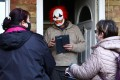 Volunteers hand out a Covid-19 home test kit to a resident wearing a clown mask in Woking, Britain on Tuesday. Photo: Reuters