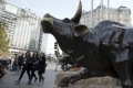 Pedestrians walk past a statue of a bull in Beijing. Alibaba recouped earlier slump to help the Hang Seng Index to a third day of gains on February 3, 2021. Photo: AP