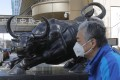 A man wearing walks by a bull sculpture in Beijing in March last year. In Hong Kong, tech stocks faltered on February 4 to end a three-day advance in the Hang Seng Index. Photo: EPA-EFE
