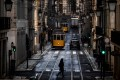 A woman crosses a street past trams in Lisbon. Photo: AFP