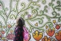 A child walks past a flower-themed mural in Kam Tin on January 2. The UN Office of the High Commissioner on Human Rights has noted that the pandemic has had serious socioeconomic impacts on children and that child protection risks are emerging daily due to efforts to contain the coronavirus. Photo: Winson Wong