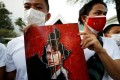 Protesters in Myanmar with a picture of Aung San Suu Kyi after the military seized power in a coup. Photo: Reuters