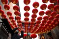 People walk under traditional Chinese lanterns along an alley in Beijing as the nation prepares to usher in the Year of the Ox on Friday. Photo: AFP