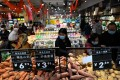 People select vegetables at a supermarket in Beijing on February 10. There is little chance of China, the growth engine of the global economy, exporting inflation any time soon. Photo: AFP