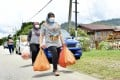 Malaysians carry shopping bags full of supplies as they walk down a deserted road amid the country's lockdown. Photo: DPA
