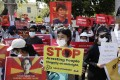 Demonstrators hold placards calling for the release of Aung San Suu Kyi and the end of nightly arrest raids, during a protest against the military coup in Yangon on February 14. Photo: EPA-EFE