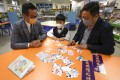 (Left to right) School principal Kwok Chiu-kwan, student Colin Choi and his father, Michael Choi, use flash cards developed by Just Feel. Photo: Jonathan Wong