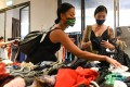 Nadia Kishlan (left) browsing through secondhand clothes at a pop-up swap event organised by a group of volunteers in Singapore. Photo: AFP