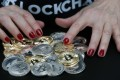 In this photo illustration, a woman shows different visual representations of cryptocurrencies, Ripple, Bitcoin, Litecoin and Ethereum on February 01, 2018 in Paris, France. Photo: Getty Images