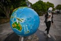 A woman wearing a face mask looks at a globe in a park in the Chinese city of Wuhan in April 2020. Photo: AFP