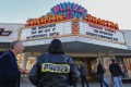 An off-duty police officer hired by the cinema stands watch as people arrive to watch the controversial movie The Interview at the Plaza Theatre in Atlanta, Georgia, in December 2014. The Sony Pictures comedy was the subject of threats by North Korea after a hacking attack. Photo: EPA