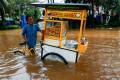 A street vendor pushes his cart through the water in an area affected by floods following heavy rains in Jakarta, Indonesia on Saturday. Photo: Reuters