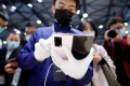 An employee of Huawei Technologies Co shows the company's new 5G Mate X2 foldable smartphone to visitors at telecommunications industry trade show MWC Shanghai on February 23, 2021. Photo: Reuters