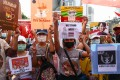Pro-democracy protesters holds signs relating to the #MilkTeaAlliance and the current situation in Myanmar as they take part in a demonstration in Bangkok on Sunday. Photo: AFP