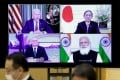 """A monitor in Tokyo displays the virtual """"Quad"""" meeting on Friday of (clockwise from top left) US President Joe Biden, Japan's Prime Minister Yoshihide Suga, India's Prime Minister Narendra Modi and Australia's Prime Minister Scott Morrison. Photo: AFP"""