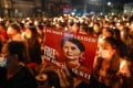 A protester in Yangon holds a poster with an image of detained civilian leader Aung San Suu Kyi. Photo: AFP