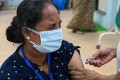 An Indian woman gets inoculated with a dose of the AstraZeneca vaccine. Photo: AFP
