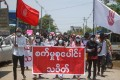 """Demonstrators carry a banner that reads """"Industrial Strike Group"""" during a protest in Mandalay. Photo: EPA"""