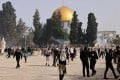 Palestinians run for cover from tear gas fired by Israeli security forces at Jerusalem's Al-Aqsa mosque compound on Monday. Photo: AFP