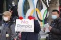 A protester holds a placard during an anti-Olympics rally outside the Japan Olympic Museum in February. Photo: DPA