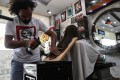 Pakistani barber Ali Abbas uses a blowtorch to cut the hair of a customer at his shop in Lahore. Photo: AFP