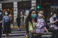 People cross the street in Shanghai on May 11. China must make a whole-of-society push to raise the birth rate, and this must include making childcare more accessible to working families. Photo: EPA-EFE