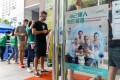 People queue near a poster advertising Hong Kong's vaccination programme outside a community vaccination centre in April. Photo: Bloomberg