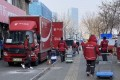 Drivers move parcels from a delivery truck to their own vehicles at a JD Logistics distribution station in Chaoyang district, Beijing, on February 26, 2021. Photo: Minghe Hu