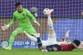 Qingdao FC's Radonjic (centre) goes down under a strong challenge during the match against Chongqing. Photo: Xinhua