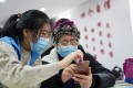A student volunteer from Beijing Foreign Studies University teaches as a senior resident learns how to use a health-tracking app, introduced amid the COVID-19 outbreak. Photo: Xinhua