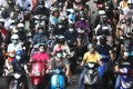 Moped riders in Tapei, Taiwan, wait at a traffic light on May 18. After keeping Covid-19 under control for months, Taiwan is grappling with a recent wave of infections. With many societies still far from achieving herd immunity, we need to be prepared to coexist with the virus over the coming years. Photo: Reuters