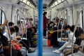 Face mask-clad passengers use their smartphones while riding the subway in Wuhan, in China's central Hubei province. Photo: AFP