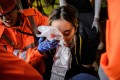 Medics look after a woman who received a facial injury during a stand-off between protesters and police in Tsim Sha Tsui in Hong Kong on August 11, 2019. Photo: AFP