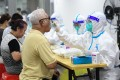 A medical worker collects swab samples in Guangzhou's Liwan district. Photo: Xinhua