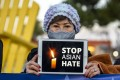 """A woman holds up an iPad with the message """"Stop Asian Hate"""" during a vigil in California in honour of victims of the Atlanta-area spa shootings in March. Photo: DPA"""