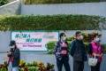 """A banner promotes the Covid-19 inoculation programme as people wait outside a community vaccination centre in Hong Kong on March 10. The """"wait and see"""" approach many Hongkongers have taken to vaccination is stalling economic recovery. Photo: Bloomberg"""