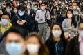 Passengers wearing masks walk through Central MTR station in Hong Kong on February 18. Photo: Bloomberg