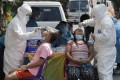 Health workers conduct a Covid-19 swab test on residents in Quezon City, Philippines. Photo: AP