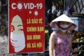 A woman walks past a sign bearing Covid-19 prevention advice in Hanoi. Photo: EPA-EFE