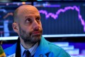 A trader looks anxiously at screens during the opening bell at the New York Stock Exchange in February 2020. If the Fed has to tread lightly for fear of frightening the markets, other central banks such as China's are being less reticent. Photo AFP