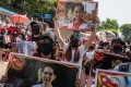 Protesters hold placards with portraits of Aung San Suu Kyi during a demonstration in February. Photo: TNS
