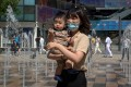 A woman holds her child outside a shopping centre in Beijing on June 1, a day after China announced it would allow couples to have three children. Photo: AFP