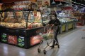 A woman shops in a supermarket in Beijing. In China, factory gate inflation has accelerated to 9 per cent but consumer price inflation stands at 1.3 per cent for May. Photo: EPA-EFE