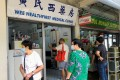 People are seen outside a clinic in Singapore that offers the Chinese-made Sinovac coronavirus jab. Photo: Reuters