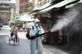 A soldier wearing full protective suit disinfects a public area in Taiwan. Photo: DPA