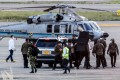 Colombia's President Ivan Duque, fourth from right, and bodyguards near the presidential helicopter at Camilo Daza International Airport after it was hit by gunfire in Cucuta, Colombia on Friday. Photo: Colombian Presidency / AFP