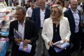 Far-right leader Marine le Pen and local candidate Thierry Mariani (left) campaign at a market in southern France. Photo: AP