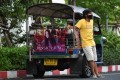 Samran Thammasa stands next to his tuk tuk bearing a banner of K-pop star Jessica Jung. Photo: Reuters